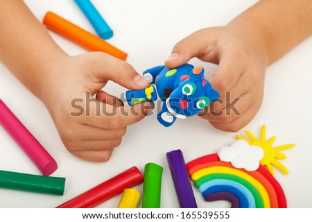 Child playing with colorful clay making animal figures - closeup on hands - stock photo