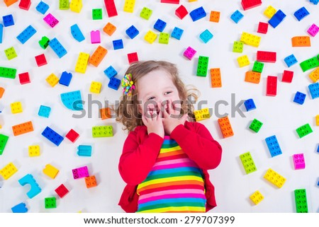 Child playing with colorful toys. Little girl with educational toy blocks. Children play at day care or preschool. Mess in kids room. View from above. - stock photo