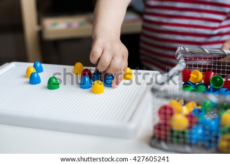 Child playing with colorful toys sitting at a window. Little boy with educational toy. Children play at day care or preschool. Mess in kids room. - stock photo