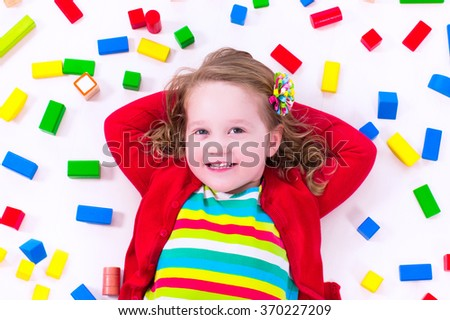 Child playing with colorful wooden toys. Little girl with educational toy blocks. Children play at day care or preschool. Mess in kids room. View from above.