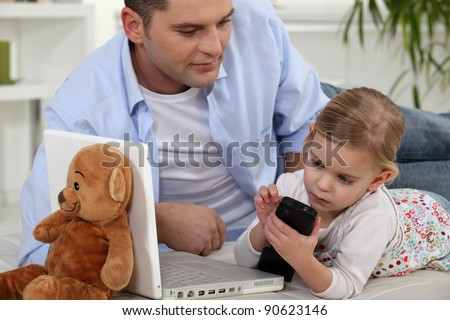 Child playing with Daddy's cellphone - stock photo