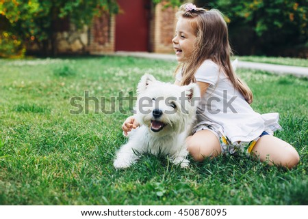 Child playing with English Highland White Terrier dog on grass in the backyard - stock photo