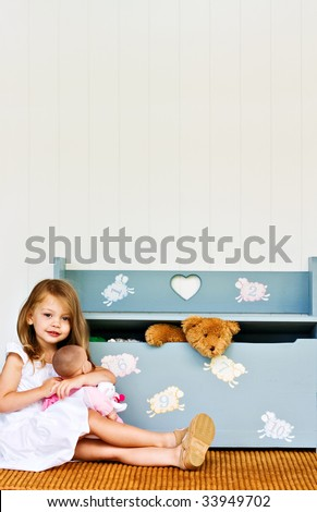 Child playing with her doll while a teddy bear pokes his head out of the toy chest.