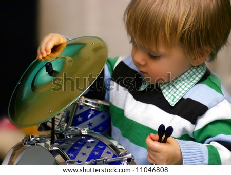 Child playing with his drums, looking under the cymbals, Looking for something - stock photo