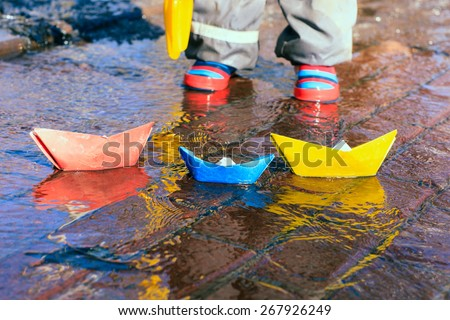 child playing with paper boats in spring water puddle - stock photo