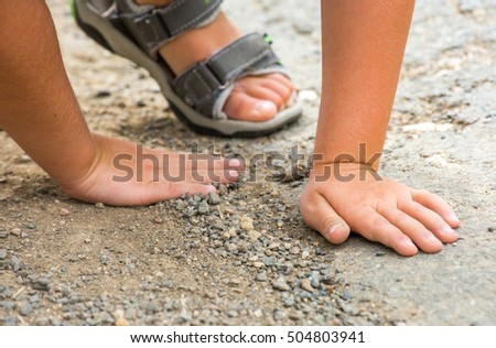 child playing with pebbles on the floor