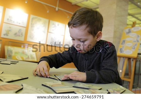 Child playing with puzzle in the classroom - stock photo