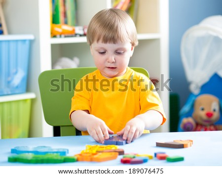 child playing with puzzle toy indoor - stock photo