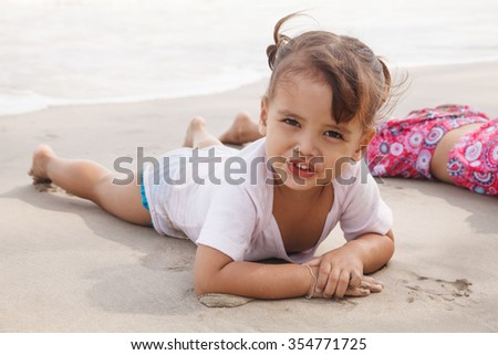 Child playing with sand at the beach in summer.
