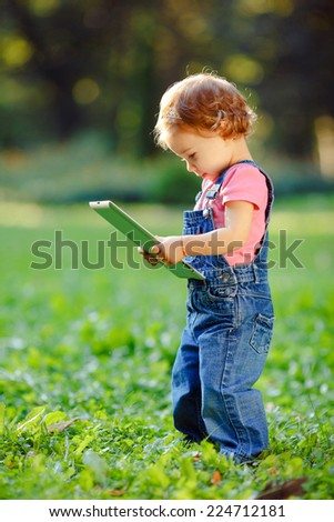 Child playing with tablet outdoors. Cheerful child with a portable PC in your hands. The child looks at tablet. - stock photo