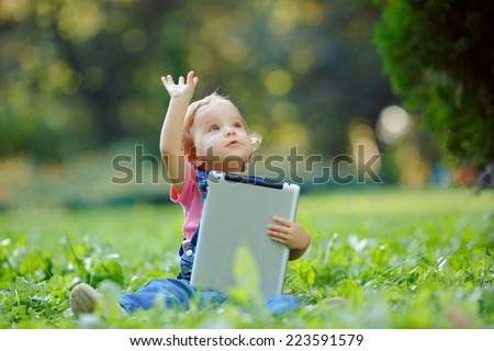 Child playing with tablet outdoors. Cheerful child with a portable PC in your hands. The kid looks away. - stock photo