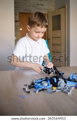Child playing with technic plastic blocks indoor. Active kid boy having fun with building and creating. - stock photo