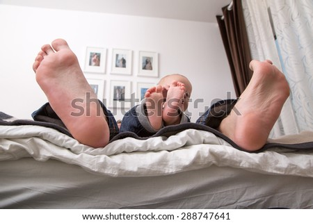 Child playing with the big toe of his father. - stock photo