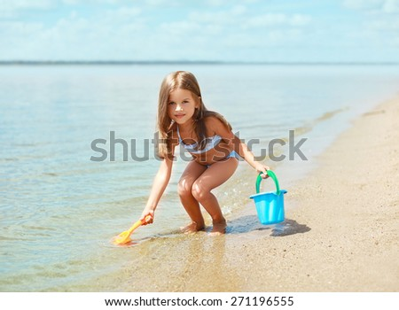 Child playing with toys and having fun on the beach near sea in summer sunny day - stock photo