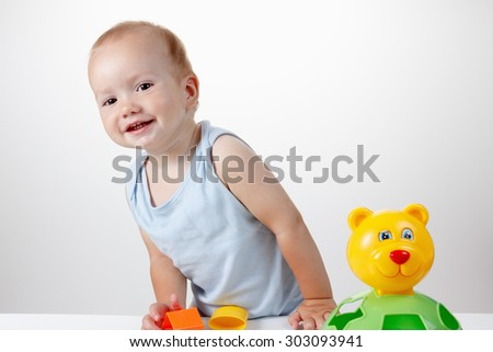 Child playing with toys in a blue dress smiling Studio - stock photo