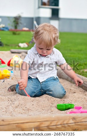 Child playing with toys on playground in sandbox - stock photo