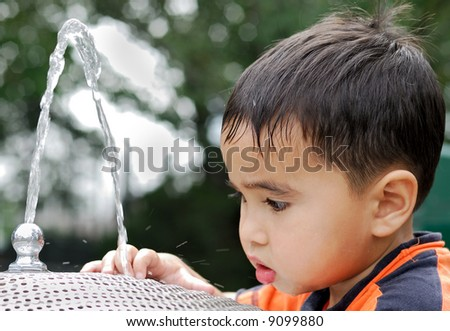 Child playing with water - stock photo