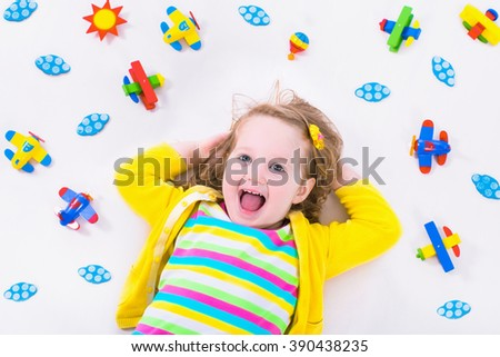 Child playing with wooden airplanes. Preschooler kid flying around the world. Kids traveling and playing. Children at day care or kindergarten. View from above. - stock photo