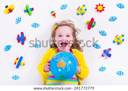 Child playing with wooden airplanes. Preschooler kid flying around the world. Kids travelling and playing. Children at day care or kindergarten. View from above. - stock photo