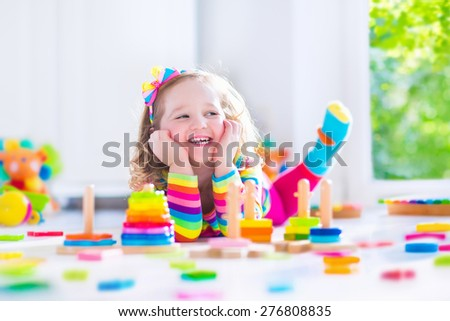 Child playing with wooden toys at preschool. Cute toddler girl having fun with toy blocks, building a tower at home or day care. Educational kids toy for nursery or kindergarten. - stock photo