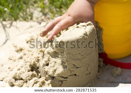 child plays builds towers of sand