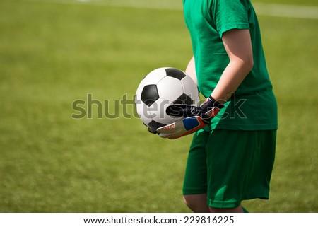 Child plays football soccer match as goalkeeper. - stock photo