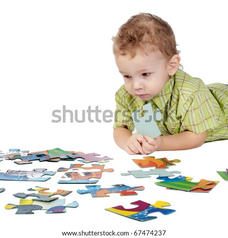 child plays with puzzles - stock photo
