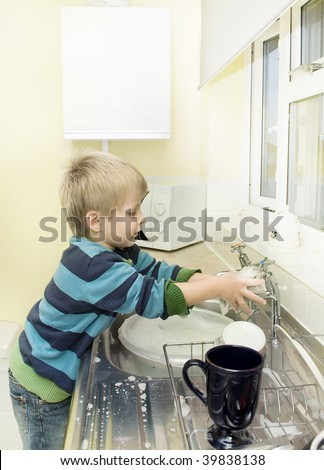 Child plays with soap and water at the kitchen sink. - stock photo