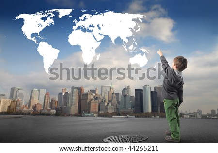 child pointing a world map and a city on the background