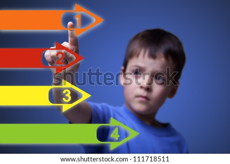 Child pointing to colorful numbered arrows on large screen - with space for your text - stock photo