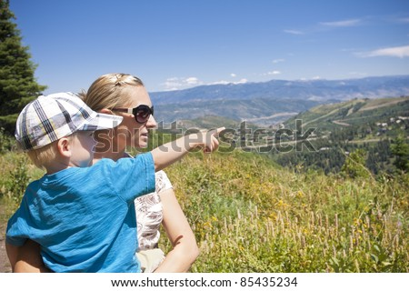 Child pointing while on a family hike in the mountains - stock photo