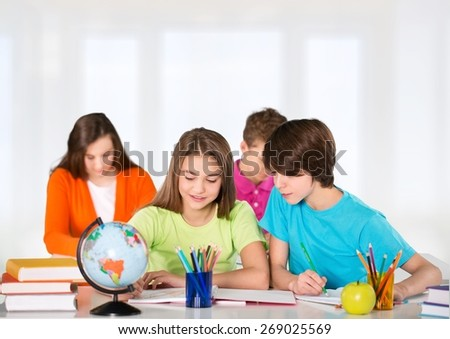 Child. Portrait of two diligent girls looking at camera at workplace with schoolboys on background - stock photo