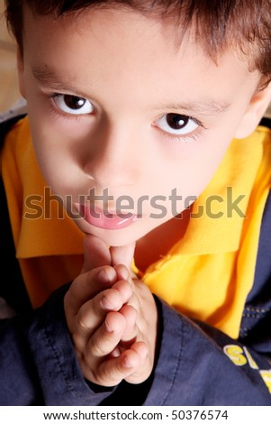 Child praying  and looking up with blue and yellow jacket - stock photo