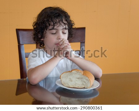Child praying for the daily bread:Curly-haired boy sits and prays with eyes closed and hands together before eating a piece of bread placed before him on the dining table. - stock photo