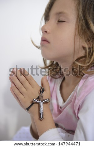 child praying to god with rosary - stock photo