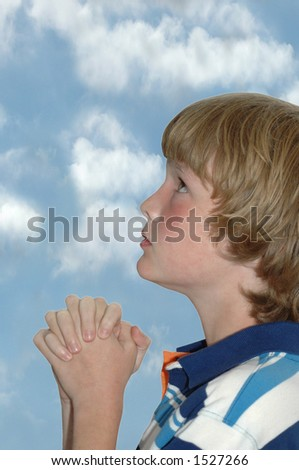 child praying with clouds (copy space above) - stock photo