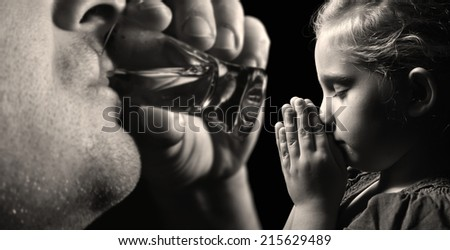 Child prays that father stopped drinking alcohol. MANY OTHER PHOTOS FROM THIS SERIES IN MY PORTFOLIO.  - stock photo