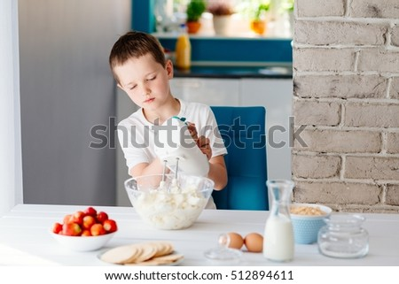 Child preparing cookies in kitchen. Mixing white cheese for cheesecake with hand mixer. Boy helping in the kitchen. Baking with children