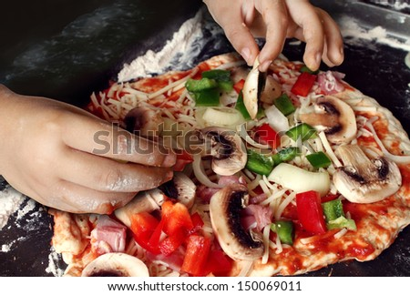 Child preparing pizza with the hands of a kid and fresh ingredients as mushrooms mozzarella cheese onions and dough as delicious food for dinner or learning how to cook at a culinary class. - stock photo