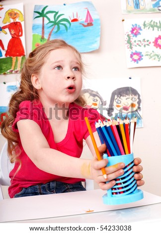 Child preschooler with pencil in play room.