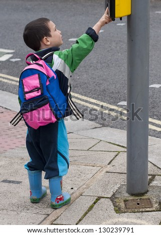Child pressing a button at traffic lights on pedestrian crossing. - stock photo