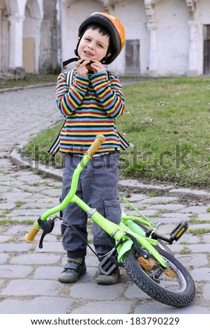 Child putting on a safety helmet and getting ready to cycle on his bicycle.  - stock photo