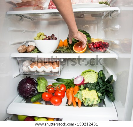 Child Reaching for Snack in Refrigerator Full of Healthy Food Options - stock photo