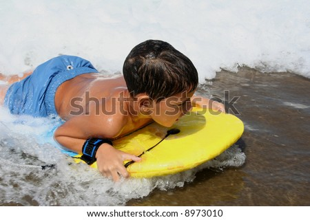 Child reaching the sand with his surfing board - stock photo