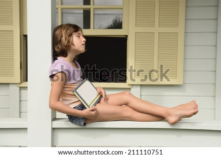 Child reading a book on balcony. - stock photo