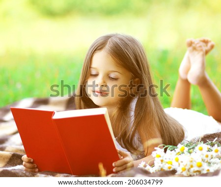 Child reading a book on the grass - stock photo