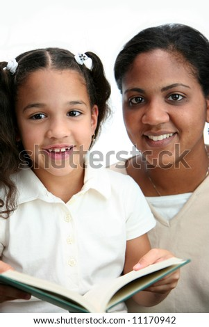 Child reading a book with her teacher - stock photo