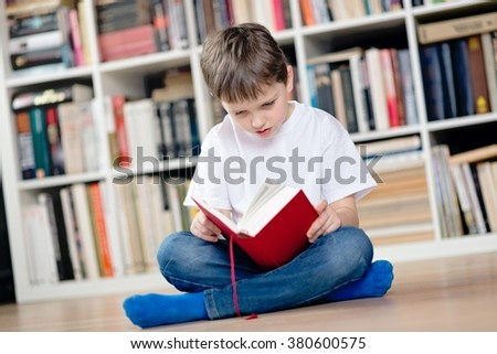 Child reading a red book in the library. He sits cross-legged on the floor. Dressed in a white t shirt and blue jeans - stock photo