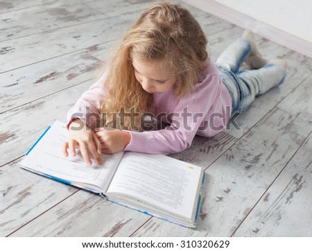 Child reading book at home. Girl doing homework - stock photo