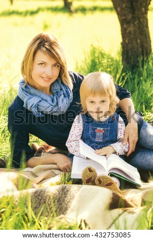 Child reading book in park with mum. Portrait of young happy mother teaching cute little girl to read. People sitting in scenic place outside on picnic blanket holding big book in hands. - stock photo